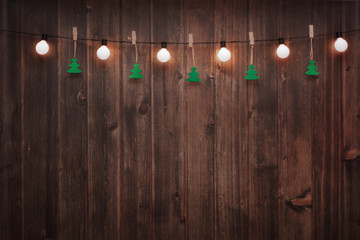 Wooden wall decorated by vintage electric lamps, Christmas or New years decoration background, space for add text or picture.