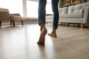 Close up of woman walking barefoot on warm wooden floor