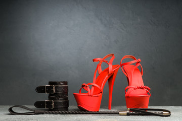 BDSM outfit for adult sex games. Red high-heeled striptease shoes and handcuffs, whip on dark background