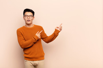 young chinese man feeling joyful and surprised, smiling with a shocked expression and pointing to the side against flat color wall