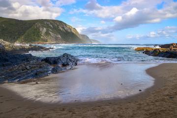 Sandy beach, blue ocean and green mountains, Tsitsikamma National Park, Garden Route, Eastern Cape, South Africa