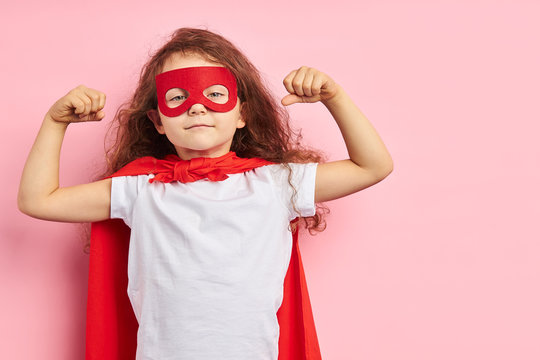 attractive little curly girl wearing red hero suit and mask showing how she is strong isolated over pink background