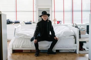 ベッドに腰掛ける、帽子を被ったシニア男性のポートレート