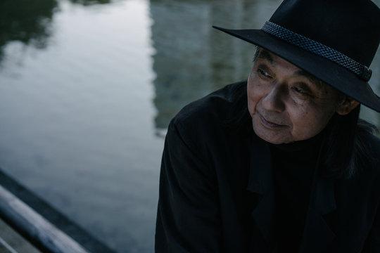 水辺で帽子を被ったシニア男性のポートレート