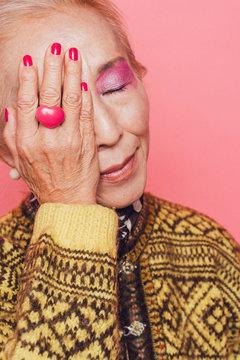 目を閉じて、顔に手を当てるシニア女性のポートレート