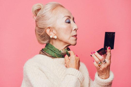 コンパクトで化粧を確認するシニア女性