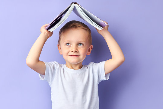 Portrait of cute caucasian child in casual clothes after education, after reading wants to play. Funny boy holding book above his head, looking up