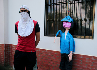 A masked university student stands next to a puppet depicting Nicaraguan President Daniel Ortega during a protest against your government at the Central American University (UCA) in Managua