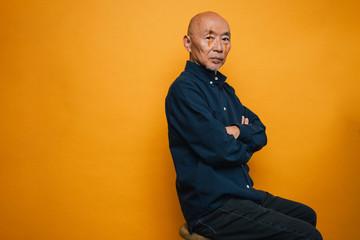 写真撮影中の座ったシニア男性のポートレート