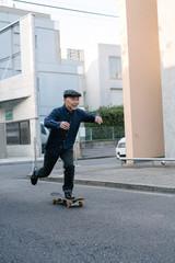 屋外でスケートボードに乗る、ハンチング帽を被ったシニア男性のポートレート