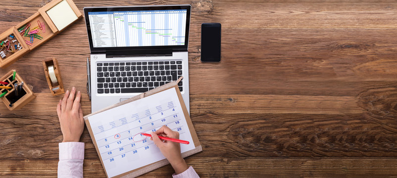 Businesswoman Scheduling The Plan Using Calendar And Laptop