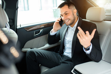 Young man inside of car wearing tux talk on phone with business colleague, while sitting in executive car, day time