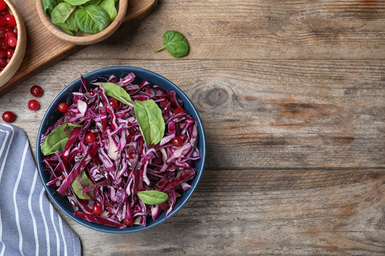 Fresh red cabbage salad served on wooden table, flat lay. Space for text