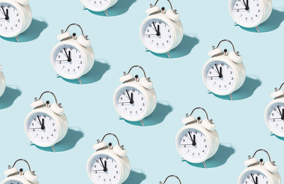 Pattern made of white alarm clocks on blue background. Trendy conceptual photo with open composition.