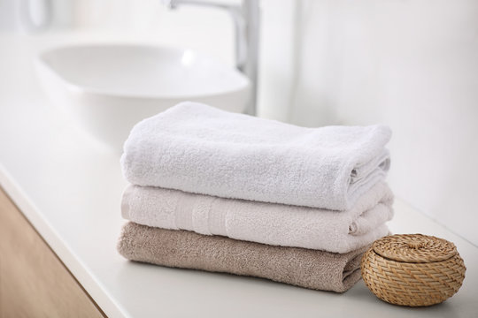 Stack of fresh towels on countertop in bathroom