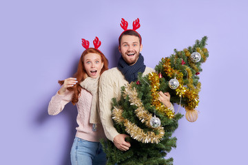 Two pretty people standing with christmas decorated fir in hands, looking at camera with joyful...