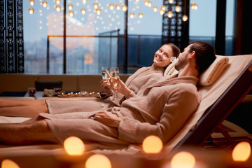 Spa, relax, enjoying concept. Married couple together relaxing in spa salon, lying on beds drinking...