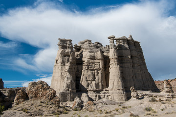 White storm cloud  and blue sky above a rock formation in Plaza Blanca near Abiquiu, New Mexico