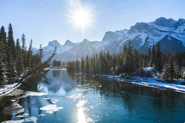 Canada Landscape. View of snow covered mountain scenery, Bow river and Three Sisters in winter. Beautiful sunny day in Canadian Rockies. Canmore, Alberta, Canada.