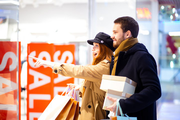 shocked woman and man wearing coats surprised with prices on clothes in shop, holding bags and gifts