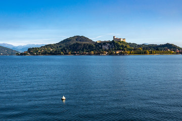 View of Borromeo Castle (Rocca di Angera) from Arona waterfront on the shores of Lake Maggiore, Piedmont, Italy