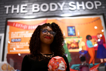 The Body Shop employee Coretta Pinson rings up merchandise at the cash register as holiday shopping accelerates at the King of Prussia Mall