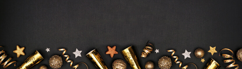 New Years Eve border banner of glittery gold stars, streamers, decorations and noisemakers. Above view over a black background.