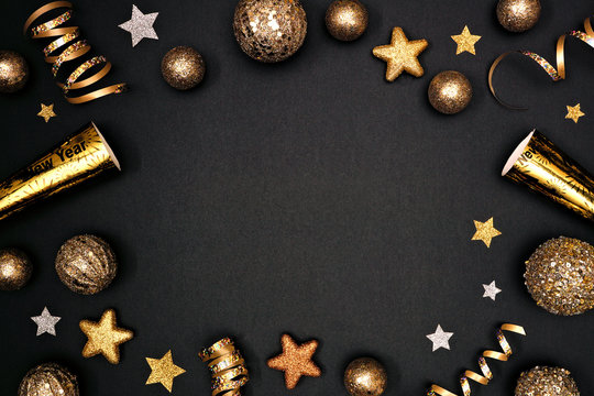 New Years Eve frame of glittery gold stars, streamers, decorations and noisemakers. Above view on a black background.