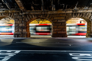 Light rail tram transportation in motion through stone archway Fotomurales