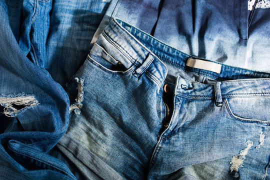 Pile of faded and ripped denim shorts and jeans in sunlight / Second-hand sustainable fashion concept
