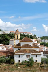 View of the white town and San Roque church with mountains to the rear, Atajate, Andalusia, Spain.
