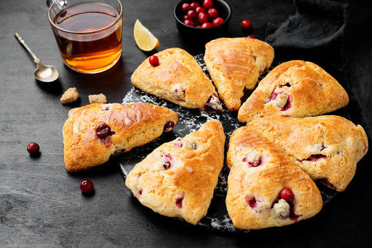 Scones with fresh cranberry  on black wooden background.
