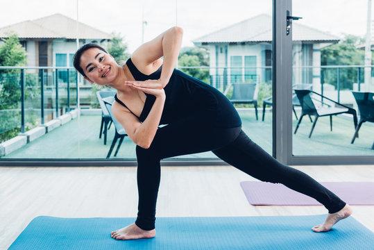 Young woman doing twist pose yoga