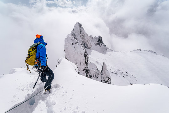 An alpinist climbing an alpine ridge in winter extreme conditions. Adventure ascent of alpine peak in snow and on rocks. Climber ascent to the summit. Winter ice and snow climbing in mountains.