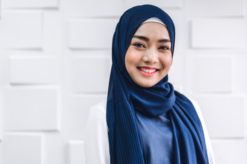 Portrait of happy arabic muslim woman with hijab dress smiling and look at camera on white wall background