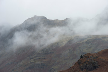 Spoed Foto op Canvas Chocoladebruin Beautiful Autumn Fall landscape image of Langdale Pikes mountain range in Lake District in mist and low cloud