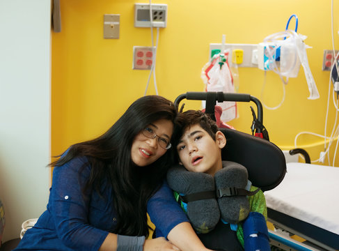 Mother talking with disabled son in wheelchair at hopsital room