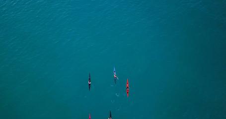 Aerial image of kayakers paddling forwards. Sport canoes and Kayaks at sea.