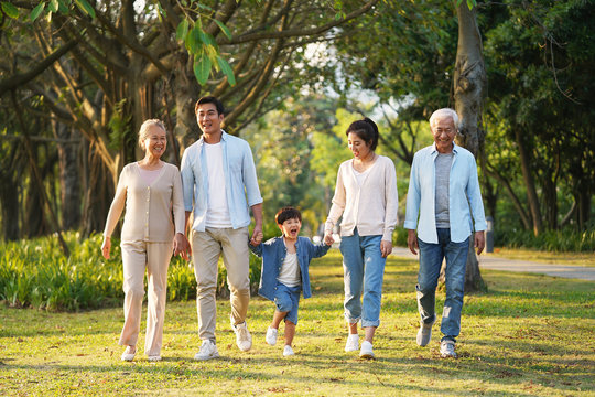 three generation asian family walking in park