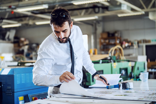 Young hardworking caucasian bearded controller looking at printed sheets and evaluates quality while standing in printing shop.