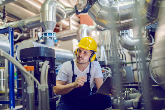 Serious caucasian handsome worker in overall, with hardhat and antiphons crouching and holding tablet while checking on motor. Factory interior.