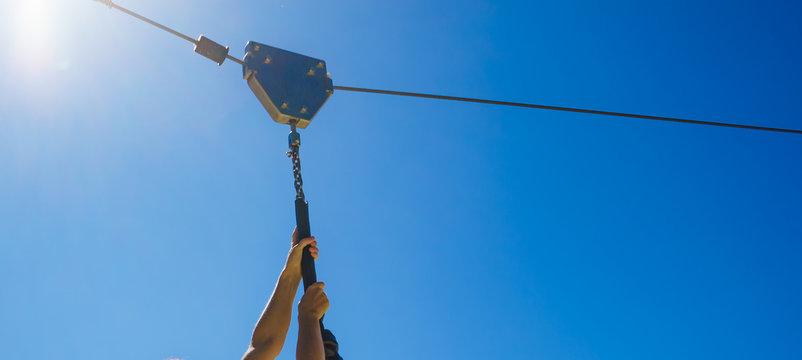 Human hands holding zipline