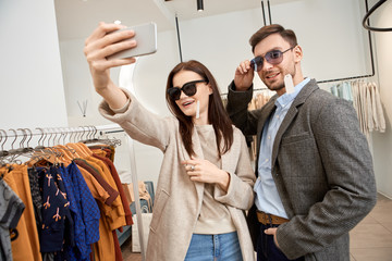 Adult woman and man making selfie in shopping mall
