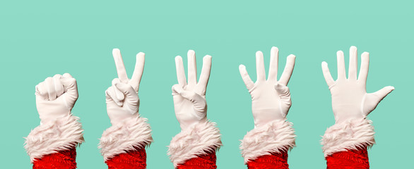 Five Santa Claus hands in white gloves on blank blue background.