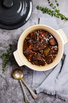 Beef bourguignon in the pot on the grey background, top view