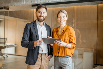 Fototapeta Portrait of a two colleagues standing together with digital tablet in creative studio. Work in marketing agency or design studio concept obraz