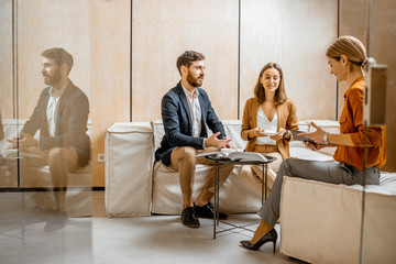 Fototapeta Young couple talking with woman as sales manager, financial advisor or psychotherapist, sitting on the comfortable couch in the office
