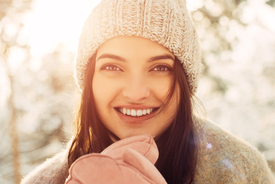 Close up portrait of a smiling girl in winter clothes in nature