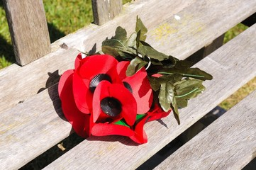 Artificial remembrance poppies on a wooden bench, National Memorial Arboretum, Alrewas, UK.
