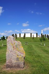 View of the Armed Forces Memorial with a large rock in the foreground, National Memorial Arboretum, Alrewas, UK.